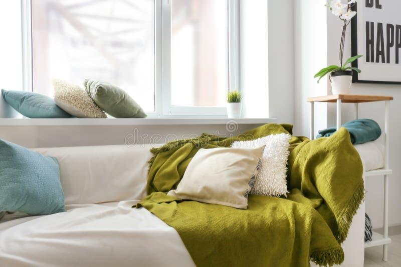 有软的格子花呢披肩和枕头的舒适沙发在窗口附近在轻的屋子里 库存图片