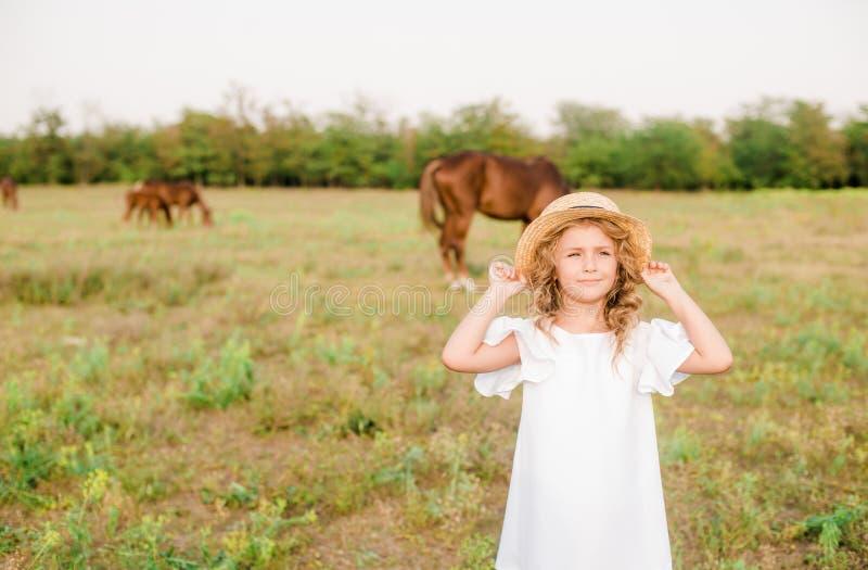 有轻的卷发的一个好小女孩在一件白色礼服和草帽调遣与马 库存图片