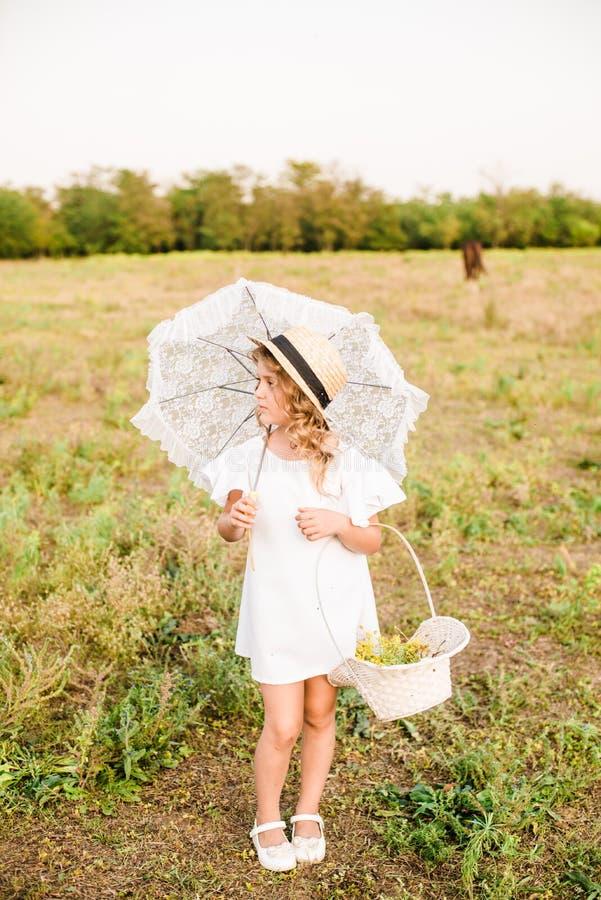 有轻的卷发的一个好小女孩在一件白色礼服和草帽调遣与马 库存照片