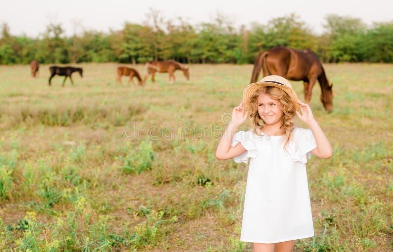 有轻的卷发的一个好小女孩在一件白色礼服和草帽调遣与马 图库摄影