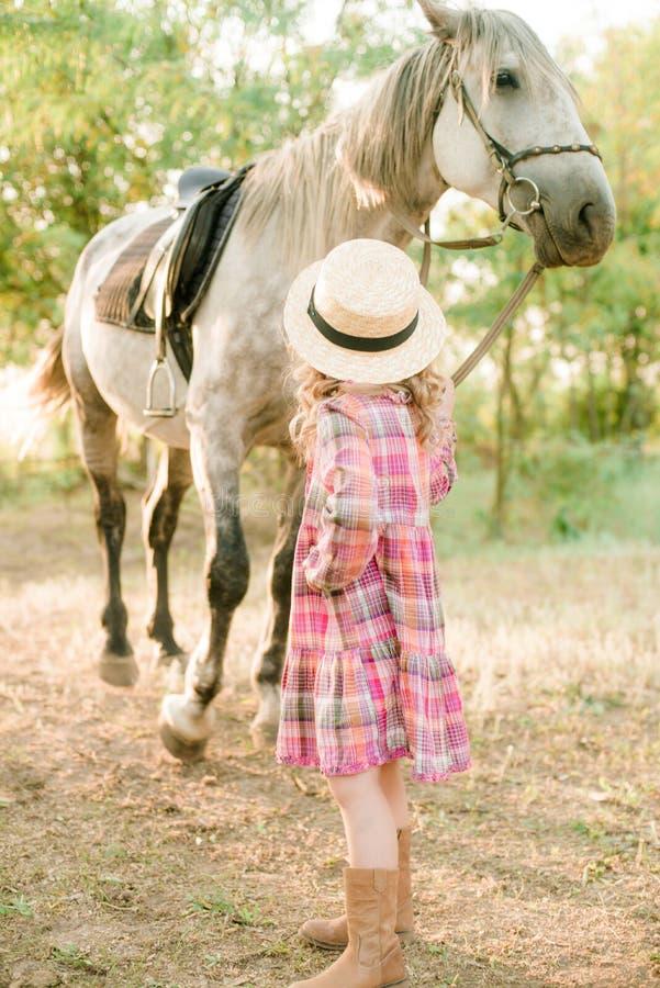 有轻的卷发的一个好小女孩在葡萄酒格子花呢披肩礼服和草帽和一匹灰色马 马a 免版税库存照片
