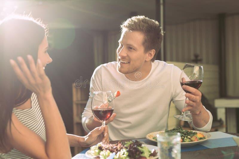 有轻的发茬的直言男朋友吃沙拉和谈话与女孩 免版税库存照片