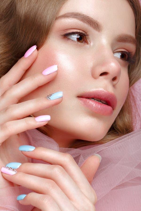 有轻的构成的美丽的女孩和在桃红色衣裳的柔和的修指甲 秀丽表面 设计钉子 库存照片