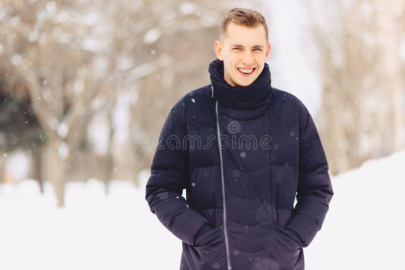 有轻的短发的一个人在对的冬天夹克姿势来了 免版税库存图片