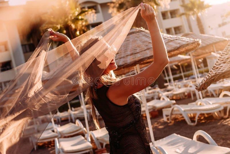有轻的织品的年轻微笑的妇女走在海滩的在塑造外形的阳光下 免版税库存图片