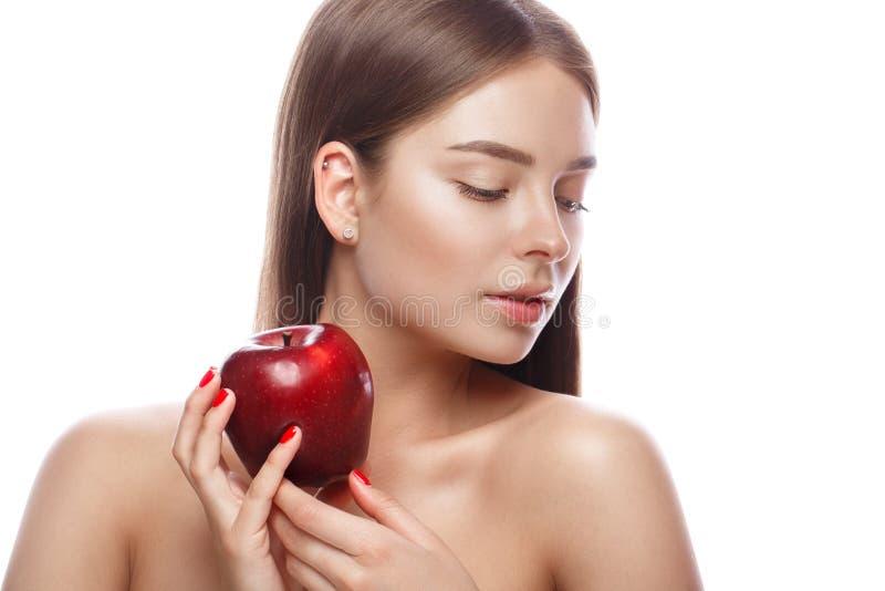 有轻的自然构成的美丽的女孩和完善的皮肤用苹果在她的手上 秀丽表面 免版税库存图片