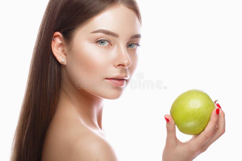 有轻的自然构成的美丽的女孩和完善的皮肤用苹果在她的手上 秀丽表面 免版税库存照片