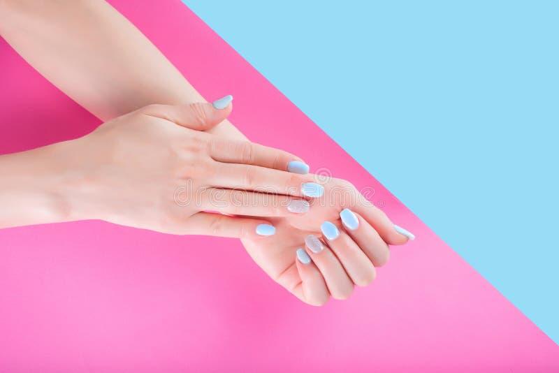 有轻轻地蓝色修指甲的女性手在粉红彩笔和蓝色隔绝的手指钉子 免版税库存照片