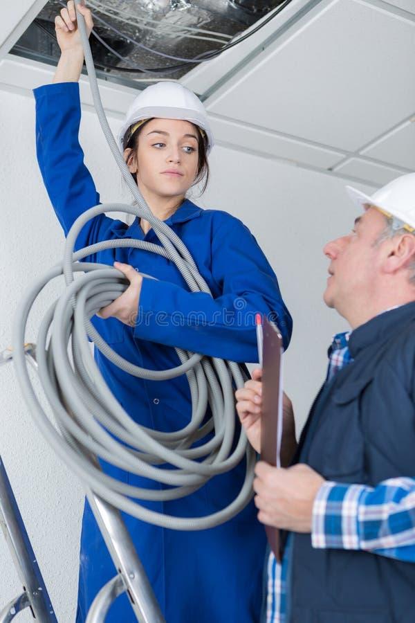 有辅导者的年轻女性电工 库存照片