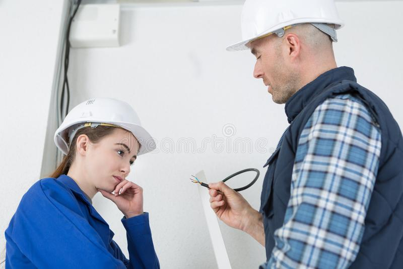 有辅导者的年轻女性电工 免版税库存照片
