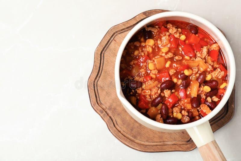 有辣豆汤、木板和空间的平底深锅在轻的背景的文本的 图库摄影