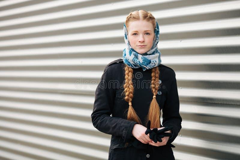 有辫子发型的年轻美丽的时兴的红头发人妇女在蓝色白色摆在outd的headcraft时髦的牛仔布黑色沟槽夹克 库存照片