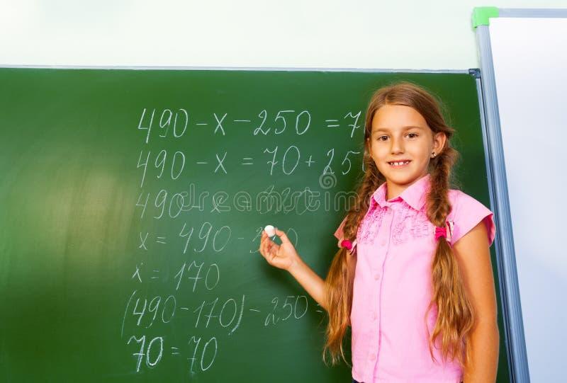 有辫子和白垩手中近的黑板的女孩 免版税库存图片