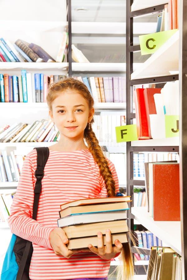 有辫子的女孩在书架附近拿着书 免版税库存图片