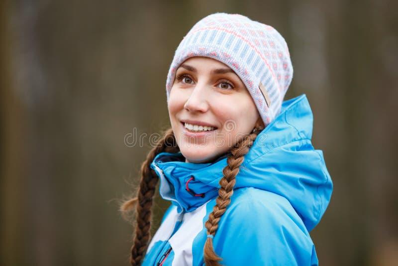 有辫子的年轻愉快的妇女在冬天活动 免版税库存照片