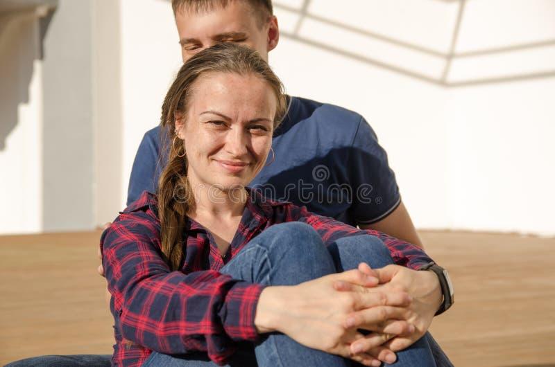 有辫子的微笑的女孩穿戴了蓝色牛仔裤,并且格子衬衫看直接照相机 免版税库存图片