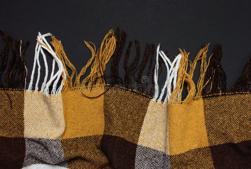 有边缘的方格的黄褐色格子花呢披肩在黑背景顶视图,拷贝空间 羊毛方格的格子花呢披肩 秋天温暖的背景 免版税库存图片