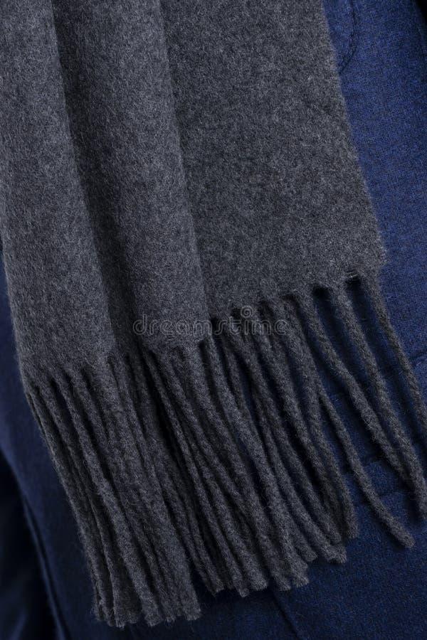 有边缘的羊毛灰色围巾在蓝色套头衫 特写镜头非常eyedroppers高分辨率视图 库存图片