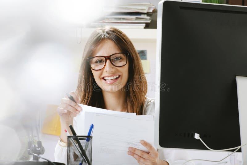 有运作在办公室的文件的少妇创造性的设计师。 免版税库存图片