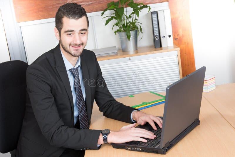 有运作在办公室的胡子的好微笑的商人坐在看他的膝上型计算机的书桌 库存照片