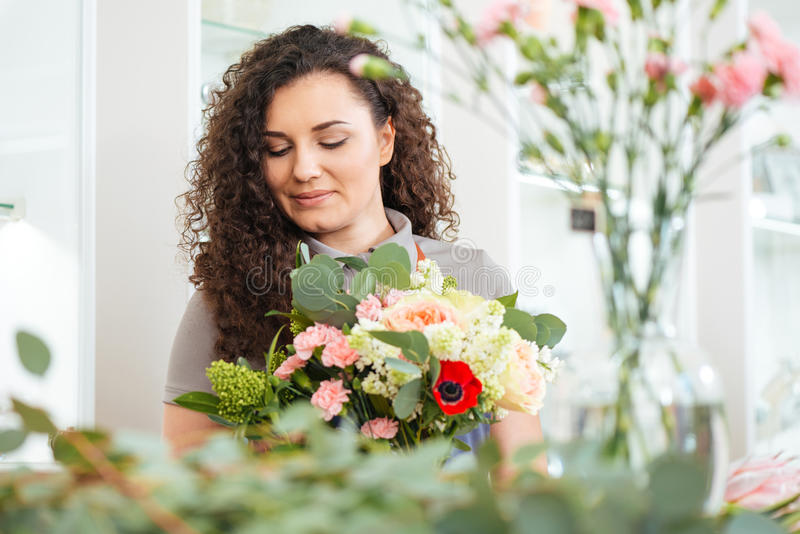 有运作在商店的花花束的可爱的妇女卖花人  库存图片