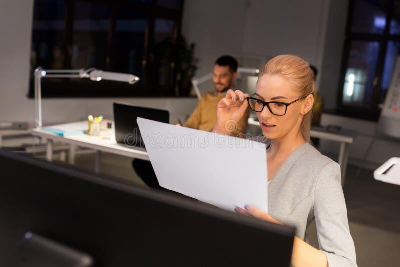 有运作在夜办公室的纸的女实业家 图库摄影