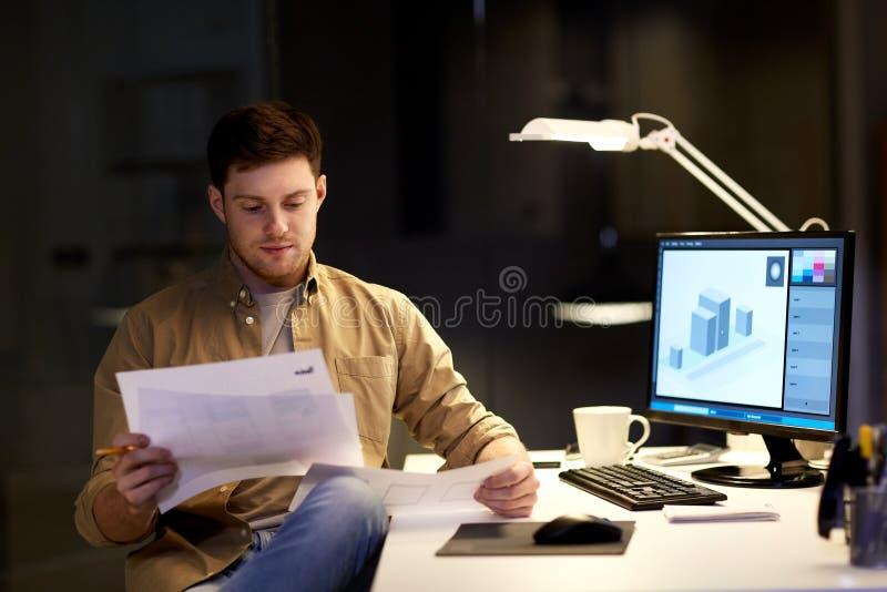 有运作在夜办公室的纸的设计师 免版税库存图片