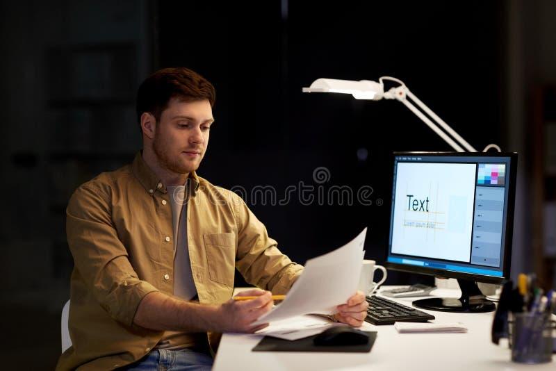 有运作在夜办公室的纸的设计师 库存照片