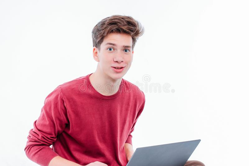 有运作在白色背景的膝上型计算机的滑稽的面孔的少年学生 库存照片