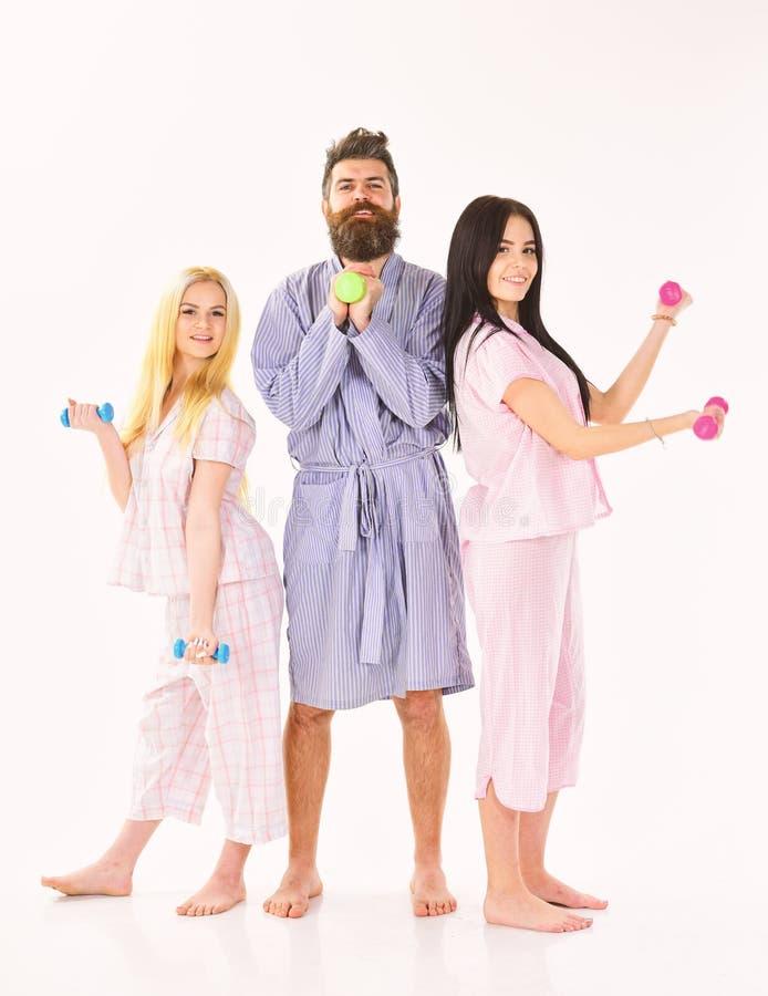 有运动的夫人的有胡子的人 教练员,强壮男子与可爱的女孩做早晨锻炼 健身早晨概念 免版税库存照片