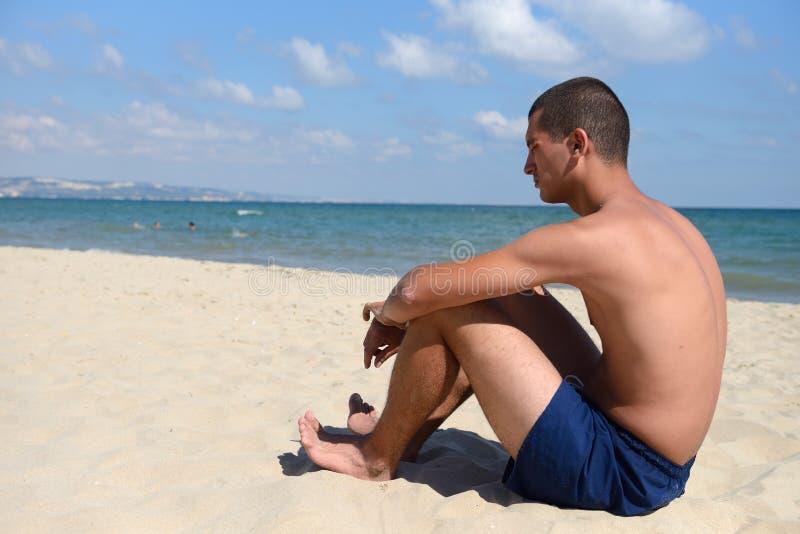 有运动身体的年轻人在站立在沙子的蓝色短裤 免版税库存图片