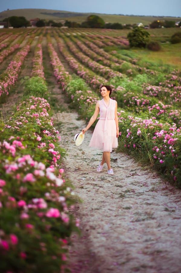 有运行沿玫瑰的黑发的美丽的年轻女人调遣 芳香、化妆用品和香水广告 库存图片