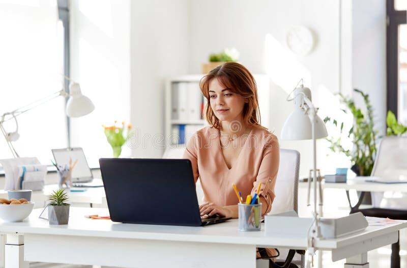 有运转在办公室的膝上型计算机的愉快的女实业家 免版税库存图片