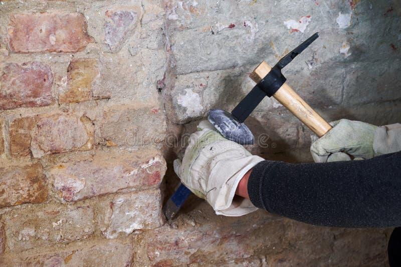 有运转在砖墙上的锤子和凿子的两只手 免版税图库摄影