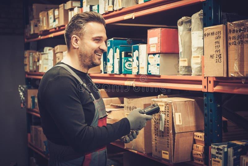 有运转在仓库里的手扶的条形码扫描器的保管员 免版税库存照片
