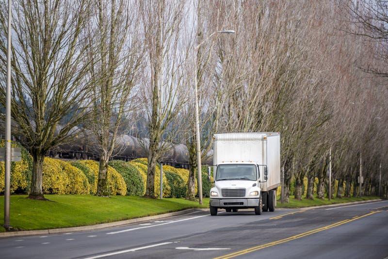 有运输在城市道路的箱子拖车的小紧凑船具卡车地方物品有树胡同和铁路的 免版税库存照片