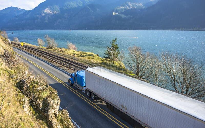 有运输物品的被冷藏的半拖车的大半船具蓝色卡车跑在沿铁路的路在哥伦比亚峡谷 库存照片