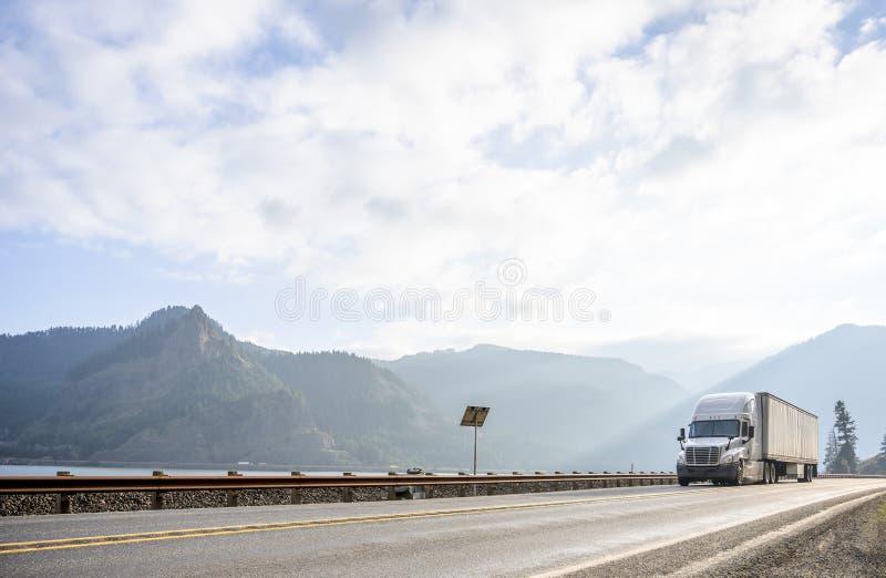 有运输carg的干燥半搬运车拖车的大半船具卡车驾驶沿河在哥伦比亚峡谷地区 图库摄影