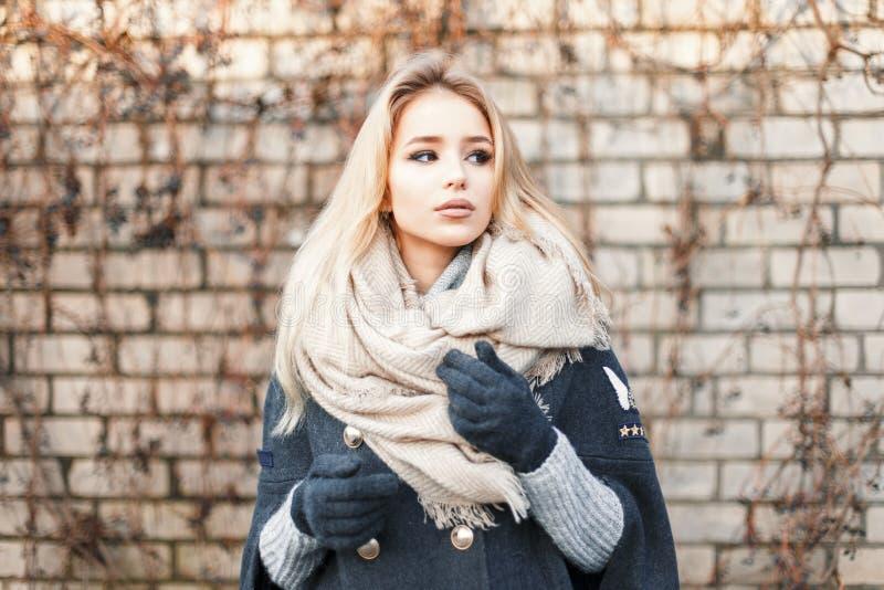 有近时兴的温暖的围巾的年轻美丽的白肤金发的妇女 库存照片