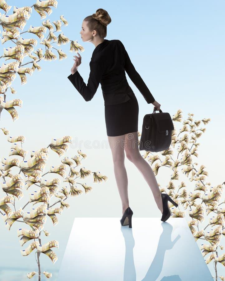 有近金钱树的逗人喜爱的女商人 免版税库存图片