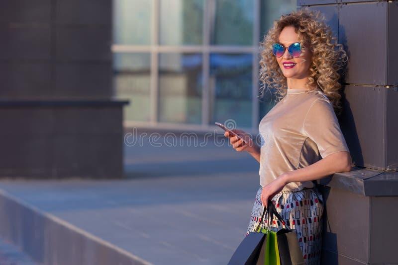 有近购物袋的叫美丽的年轻时尚的妇女购物窗口巧妙的电话,被定调子 库存照片