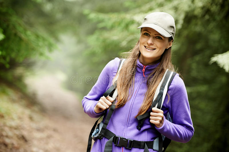 有远足入森林的背包的妇女 库存照片