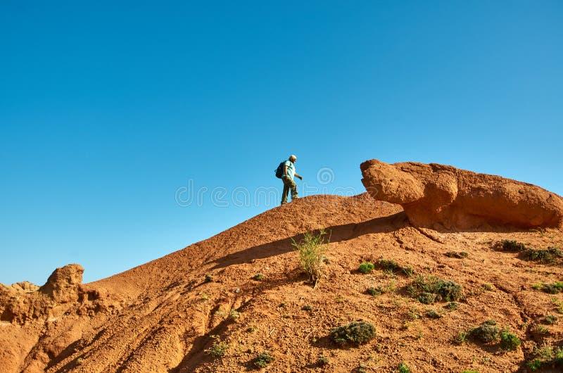 有远足在山上面的背包的白种人人  免版税库存图片