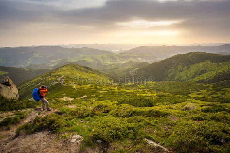 有远足在山的背包的摄影师 库存照片