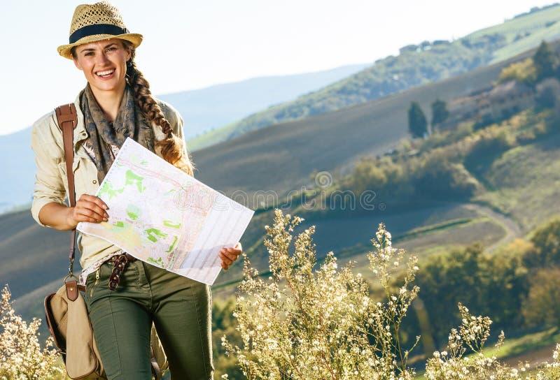 有远足在有地图的托斯卡纳的袋子的愉快的健康妇女远足者 免版税库存图片