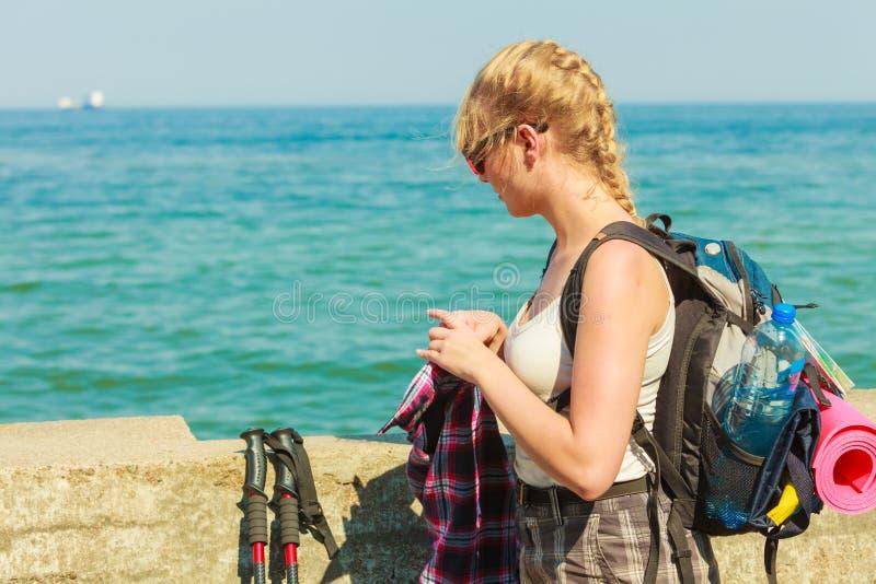 有远足在沿海的背包的少妇 免版税库存图片