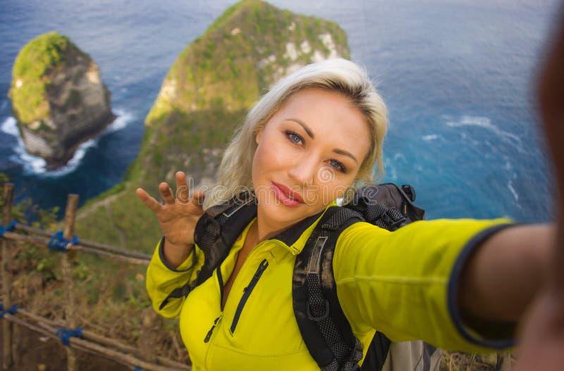 有远足在海山峭壁的背包的年轻美丽和愉快的徒步旅行者妇女采取与手机享用的selfie画象 免版税库存图片