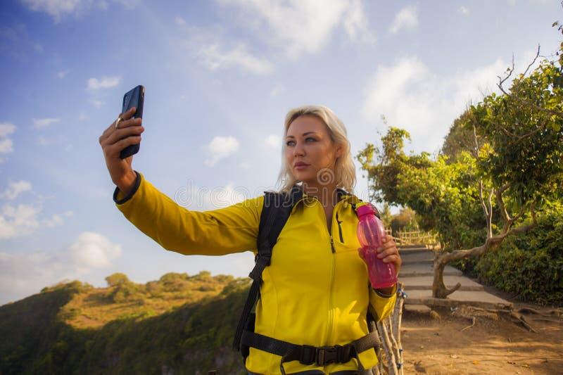 有远足在海山峭壁的背包的年轻美丽和愉快的徒步旅行者妇女采取与手机享用的selfie画象 免版税图库摄影