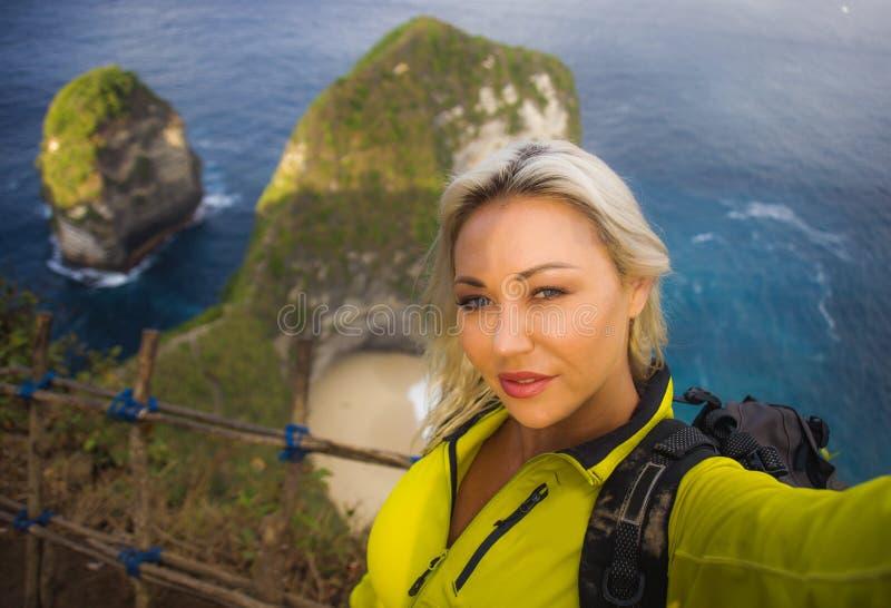 有远足在海山峭壁的背包的年轻美丽和愉快的徒步旅行者妇女采取与手机享用的selfie画象 库存图片