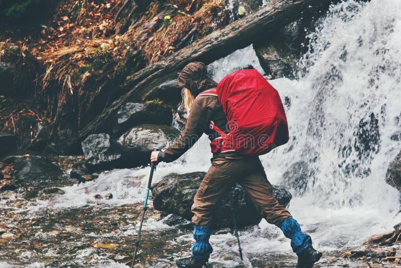 有远足在瀑布的红色背包的妇女旅客 免版税库存照片